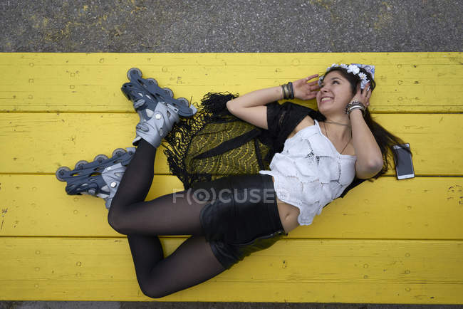 Smiling woman with inline skates lying on yellow table — Stock Photo