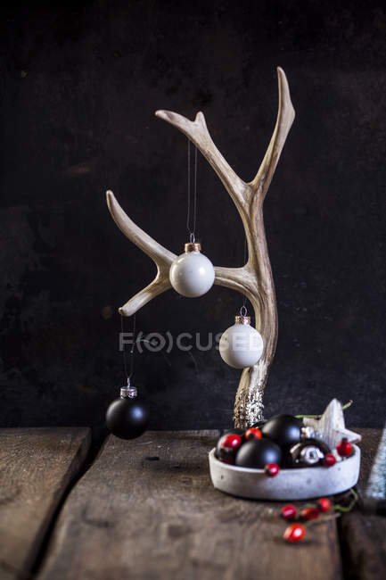 Christmas decoration with antler and  white and black baubles — Stock Photo