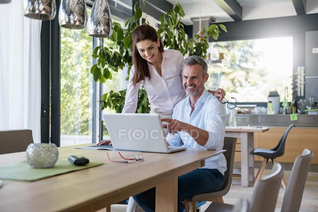 Coppia felice a tavola a casa condividendo un portatile — Foto stock