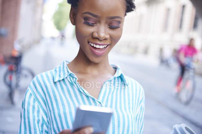 Ritratto di donna sorridente che guarda il cellulare — Foto stock