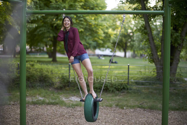 Laughing young woman having fun on a swing — Stock Photo
