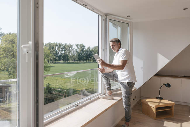 Mature man using tablet at window in empty room — Stock Photo