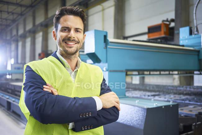 Портрет улыбающегося менеджера, стоящего на заводе — стоковое фото