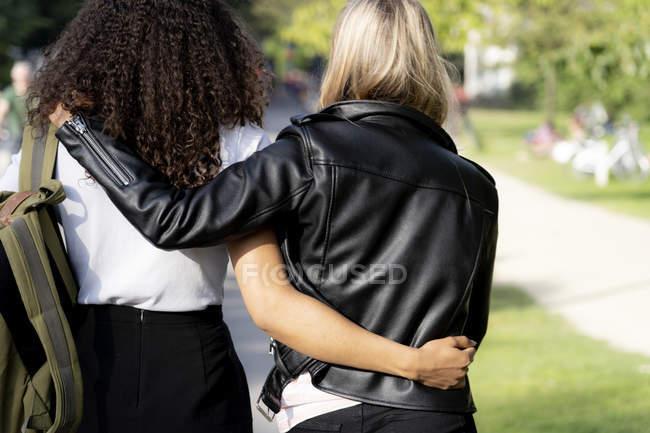 Deux copines marchant dans le parc, les bras autour, vue arrière — Photo de stock