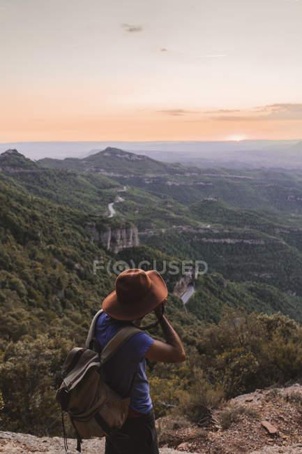 Spagna, Barcellona, Montserrat, uomo con zaino che scatta foto al tramonto — Foto stock