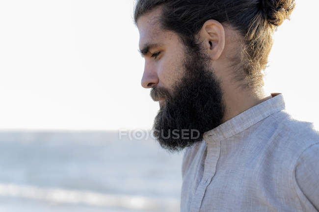 Portrait of young bearded man at sea — Stock Photo