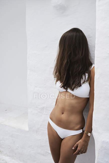 Face da coberta do cabelo da mulher nova que desgasta o biquini branco — Fotografia de Stock