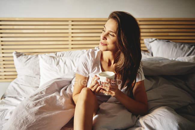 Ritratto di giovane donna sorridente seduta sul letto con una tazza di caffè che guarda a distanza — Foto stock