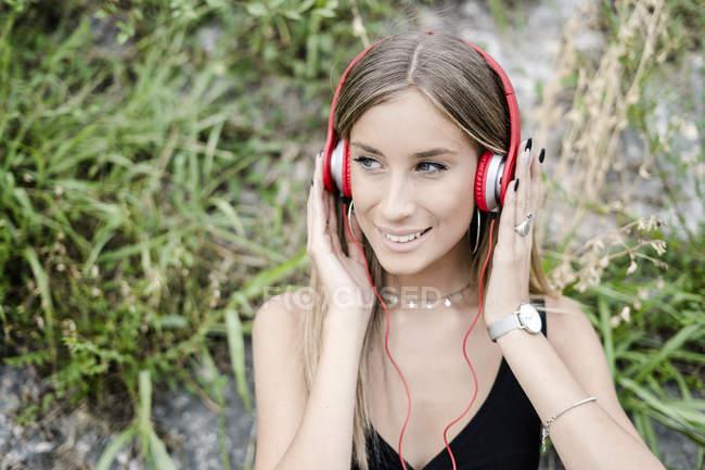 Portrait of smiling teenage girl wearing headphones outdoors — Stock Photo