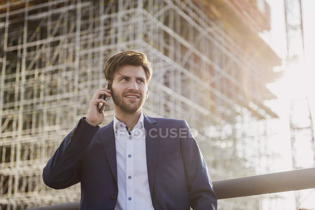 Businessman standing on bridge in front of construction site talking on cell phone — Stock Photo