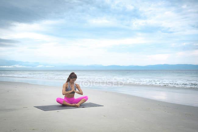 Женщина практикует медитацию йоги на пляже — стоковое фото