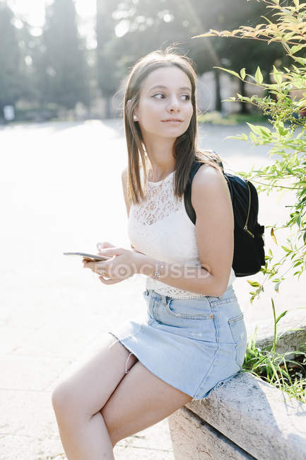 Young woman with backpack and cell phone resting in a park — Stock Photo
