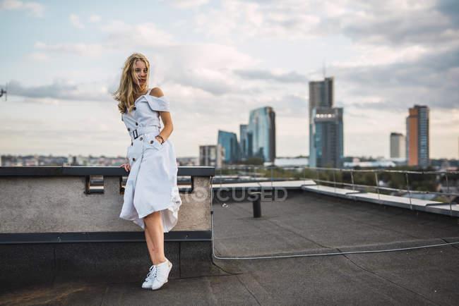 Блондинка, стоящая на террасе на крыше в белом платье — стоковое фото