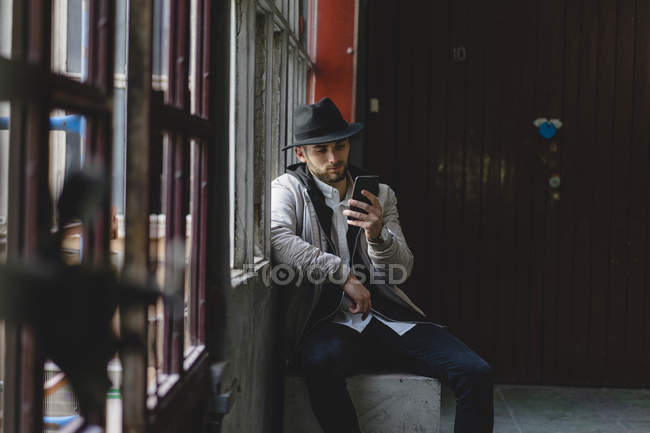 Bearded man wearing black hat, using smartphone — Stock Photo