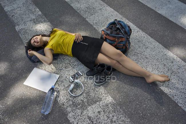 Молодая женщина, лежащая на зебре пересечения принимая перерыв — стоковое фото
