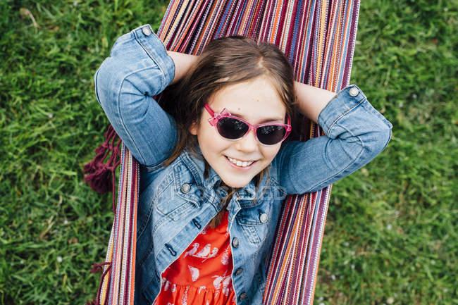 Портрет усміхнена дівчина на сонцезахисні окуляри лежачи в гамаку — стокове фото