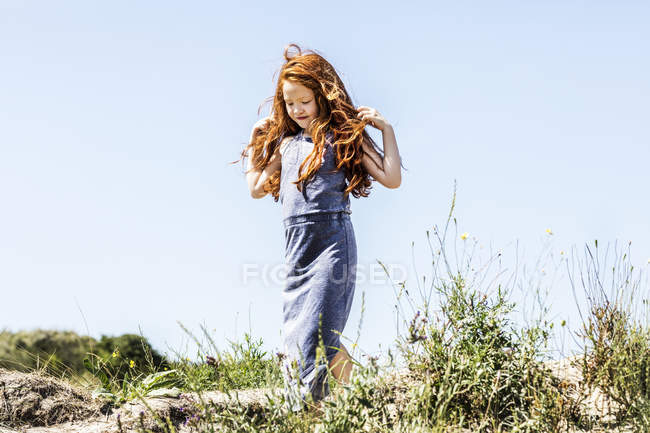 Netherlands, Zandvoort, redheaded girl walking in dunes — Stock Photo