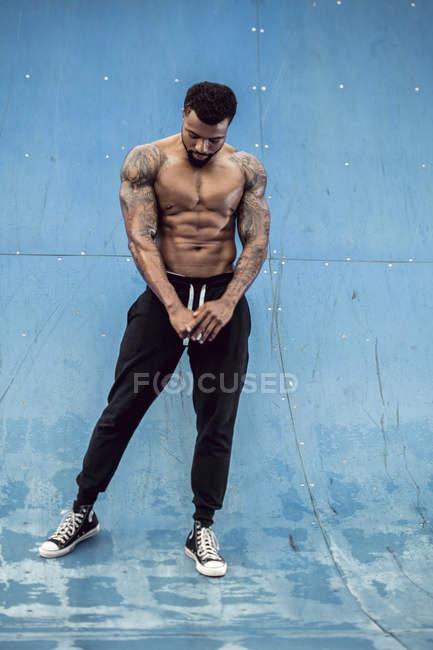 Tatuato atleta fisico in posa sul campo sportivo — Foto stock