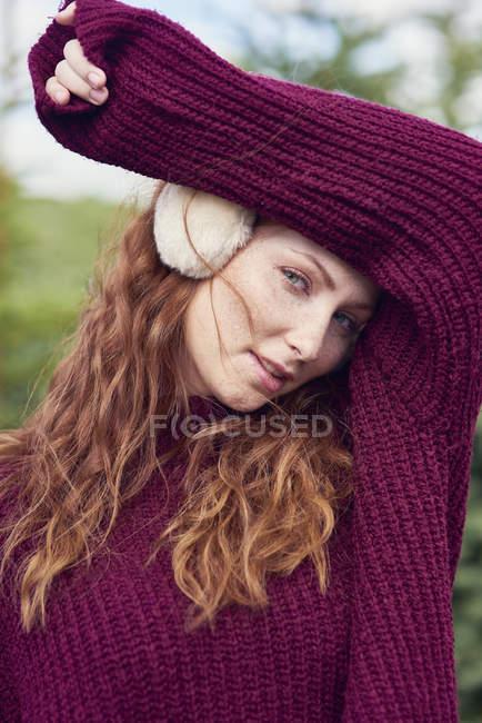 Retrato de una joven pelirroja con orejera y jersey de punto - foto de stock