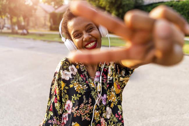 Mulher nova na moda feliz com fones de ouvido ao ar livre ao pôr do sol fazendo gesto de vitória — Fotografia de Stock