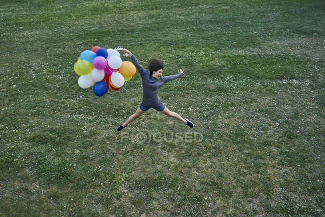 Giovane donna felice con un mucchio di palloncini che saltano in aria su un prato — Foto stock