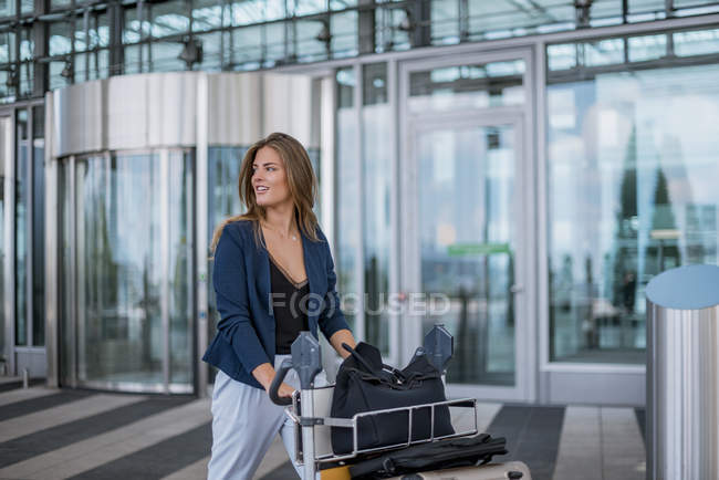 Smiling young woman pushing luggage trolley looking around — Stock Photo