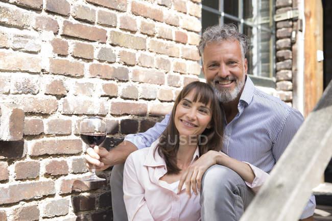 Mature couple sitting on stairs, drinking wine — Stock Photo