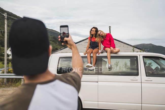 Чоловік фотографує двох дівчат, що сидять на даху фургона. — стокове фото