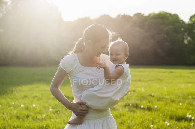 Mère et fille jouant sur la prairie en été — Photo de stock