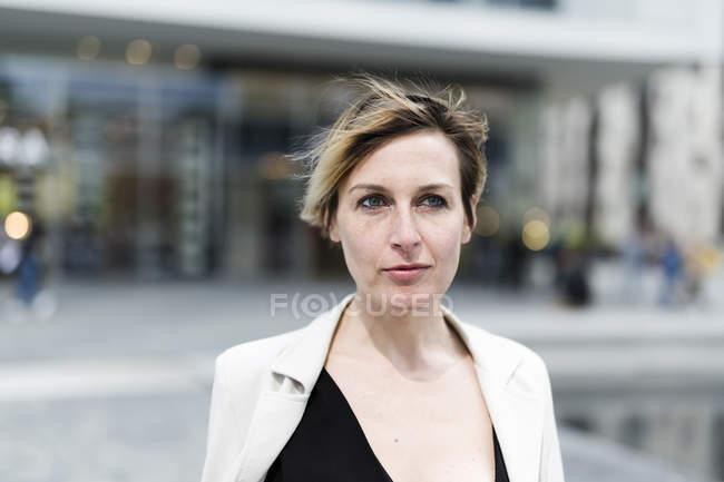 Portrait of pensive businesswoman walking in city — Stock Photo