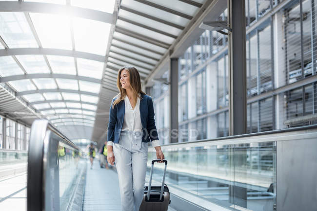 Smiling young businesswoman with baggage on moving walkway — Stock Photo