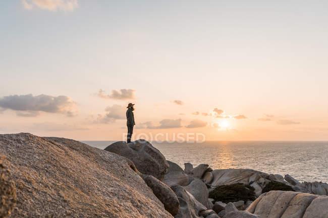 Италия, Фелиния, человек, стоящий на камне на закате, глядя на вид — стоковое фото