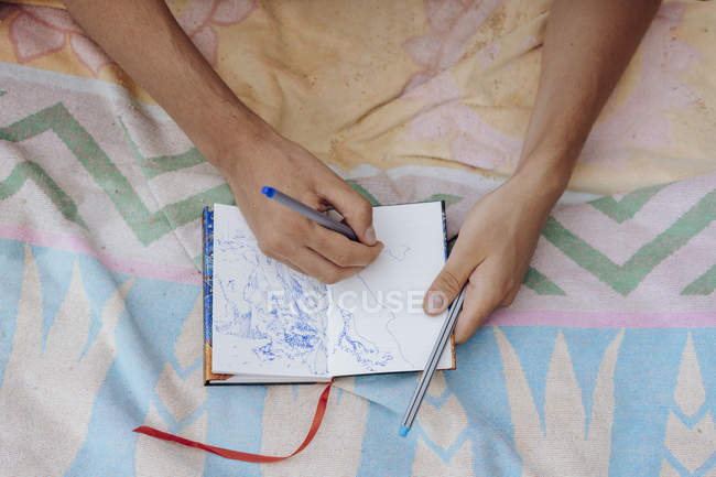 Man drawing in notebook with pen, overhead view — Stock Photo