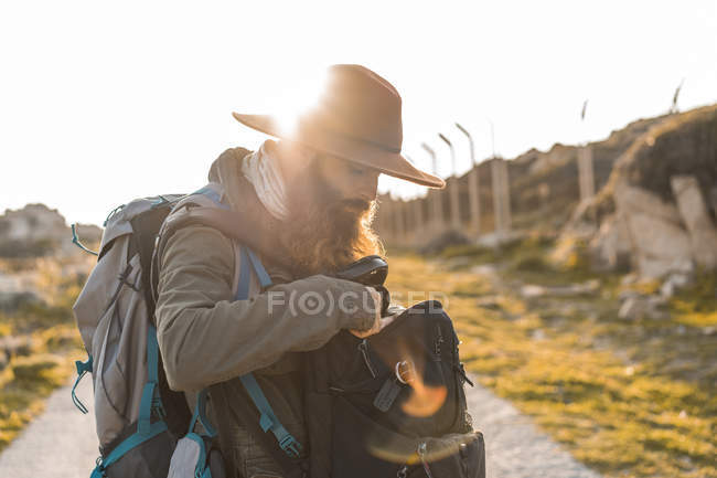 Italy, Sardinia, bearded hiker with hat and backpack at backlight — Stock Photo
