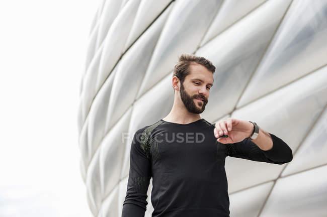 Улыбающийся спортсмен проверяет время на стадионе — стоковое фото