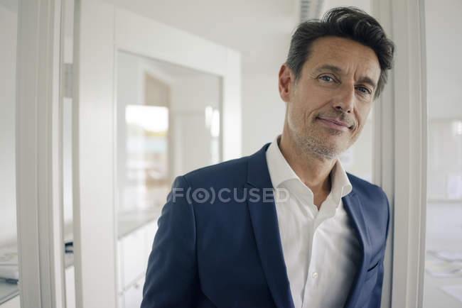 Businessman in office leaning in door frame, looking content — Stock Photo