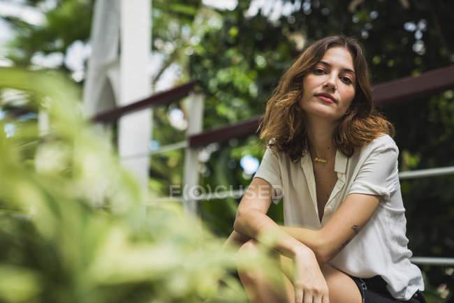 Jovem mulher sentada em estufa, retrato — Fotografia de Stock