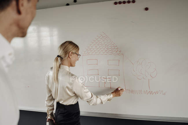 Businesswoman drawing house on whiteboard — Stock Photo