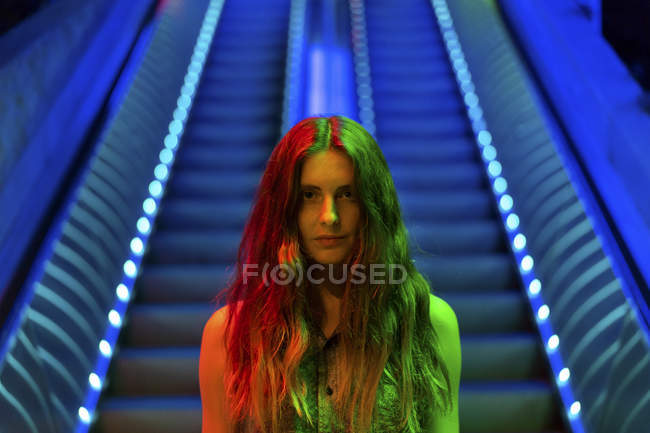 Portrait of illuminated young woman in front of blue lighted escalator — Stock Photo
