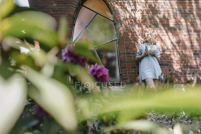 Розслаблена зріла жінка спираючись на стіну будинку в саду — стокове фото