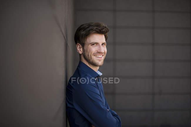 Портрет молодого улыбающегося бизнесмена, позирующего у стены — стоковое фото