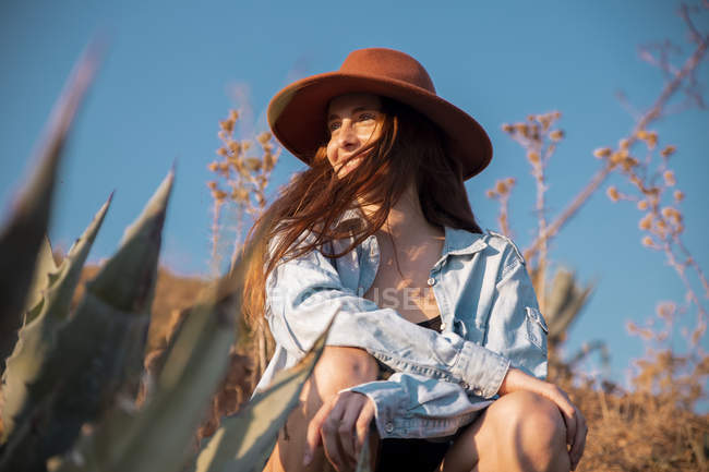 Smiling young woman wearing a hat sitting at agave in countryside — Stock Photo