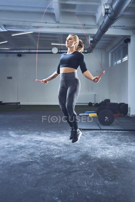 Спортивная женщина прыгает с скакалкой в спортзале — стоковое фото