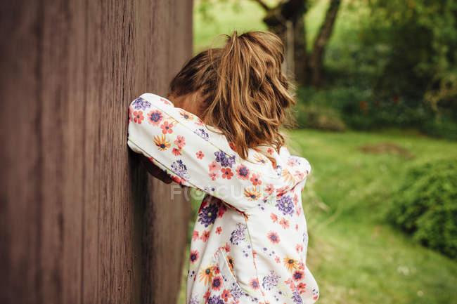 Menina que inclina-se de encontro à parede de madeira — Fotografia de Stock