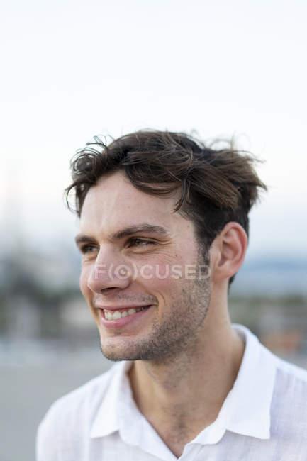 Porträt eines lächelnden jungen Mannes mit zerzausten Haaren im Freien — Stockfoto