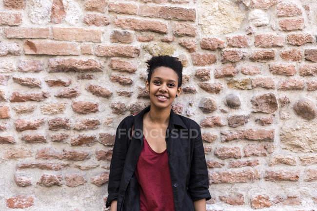 Портрет улыбающейся молодой женщины перед кирпичной стеной — стоковое фото