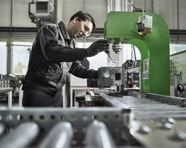 Worker in metalworking factory loading cylinder head — Stock Photo