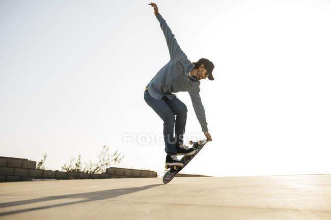 Homme à la mode dans le denim et la planche à roulettes de chapeau, restant sur la planche à roulettes — Photo de stock