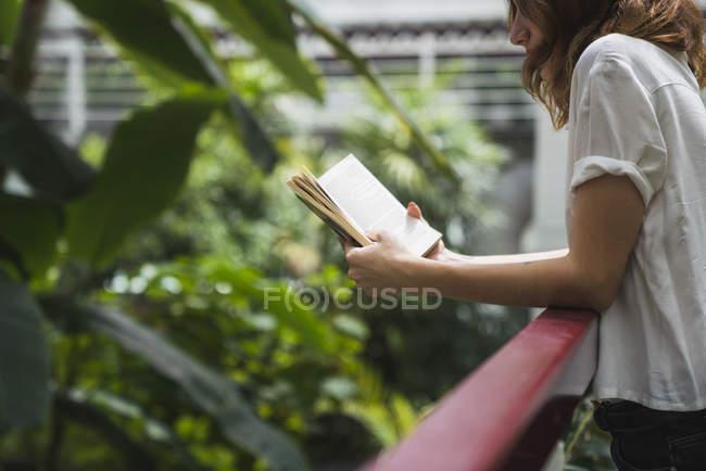 Gros plan de jeune femme lecture livre en serre — Photo de stock
