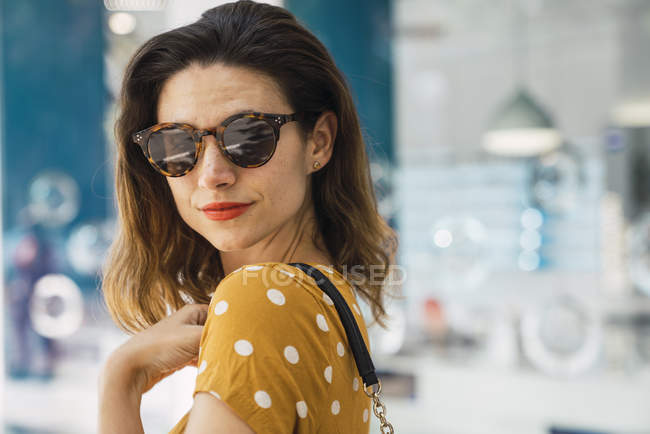 Portrait of young woman wearing yellow dress with polka dots and sunglasses — Stock Photo